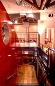 architetto_giancarlo_sottoriva_birreria_il_capolinea_piano_superiore_architettura_rosso_scala_grate_tavoli